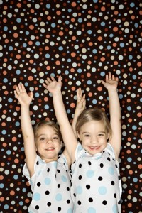 Girl twins  with arms raised.