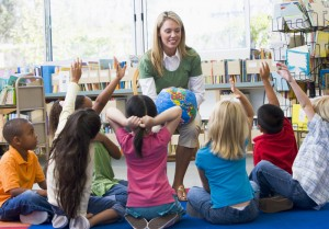 Kindergarten teacher and children with hands raised in library